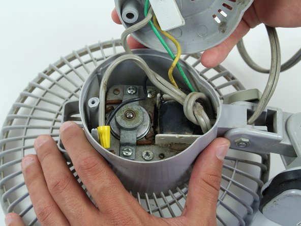 Image 3/3: Start with the fan on its back. Unscrew the back panel to expose the internal wiring.