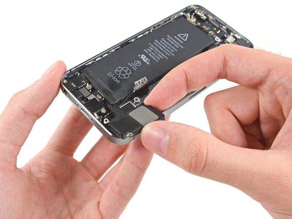 スピーカーを持ち上げ、ライトニングコネクターアセンブリからこの留めくぎを外すために、電話サイドに向けて引っ張ります。