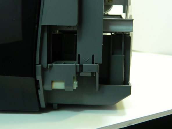 Turn the printer around so the front is facing you and gently push up on each tab of the front plastic panel, above the arrows.  Make sure the prongs are detached from the clips.