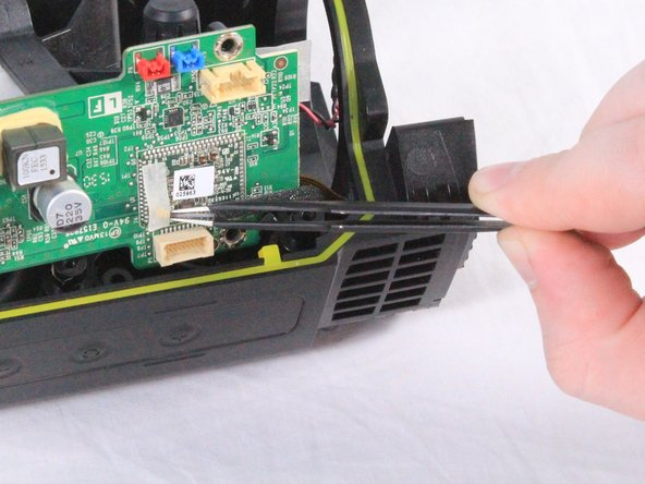There is a small coaxial cable connected underneath the motherboard. Using a pair of tweezers, carefully disconnect and remove the cable from under the adhesive tape.