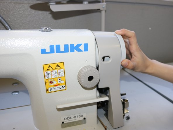 Roll the hand wheel on the right side of the machine to raise the needle up.