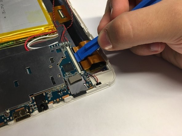 Using a plastic opening tool, lift up the latch that secures the right side of the motherboard to the screen's ribbon cable.