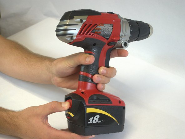 Grip the drill. Locate the red locking switch on the back of the battery. Hold the switch down.