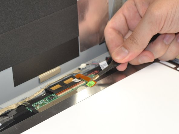 Lift up the ribbon cable contained by the adhesive strip with blunt nose tweezers.
