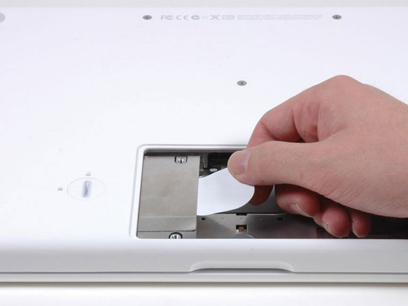 Grasp the white plastic tab attached to the hard drive and pull it to the right, removing the hard drive from the computer.