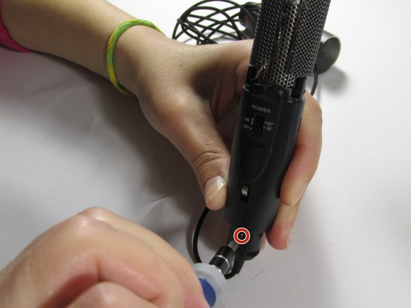 Using the Phillips head (#0) screwdriver to remove the black screw near the bottom of the microphone.
