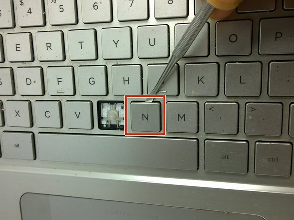 Use a metal spudger to separate key from keyboard.