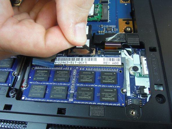 Using the pull tab, disconnect the black solid-state drive cable from the system board.