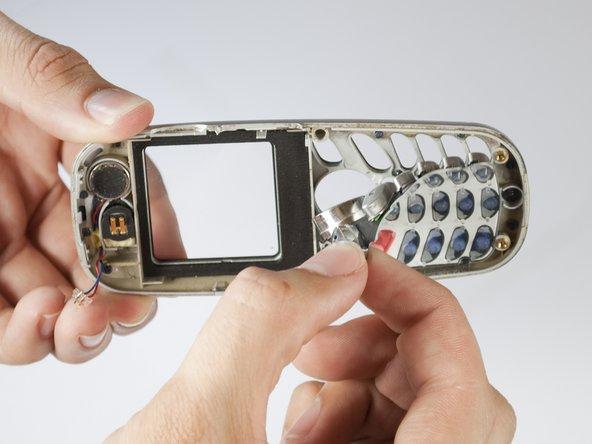 Retirez le clavier en appuyant sur les touches sur le visage du téléphone et en tirant le clavier en caoutchouc de l'autre côté.