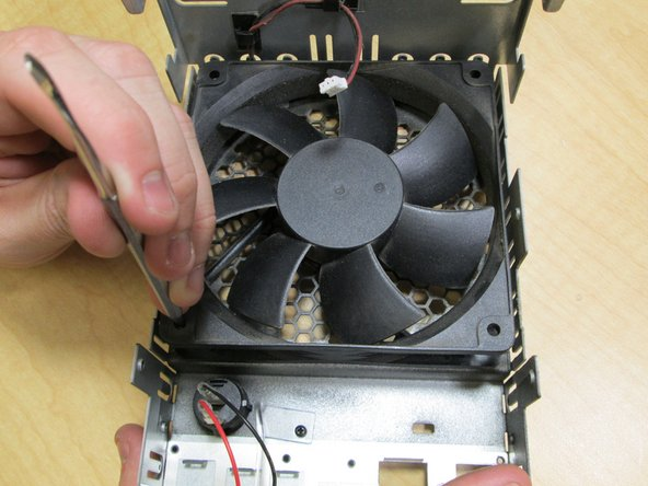 Next remove the fan by placing your screwdriver through the holes so that you can push out the small rivets.  Then unclasp the wires so that you can finally remove the fan.