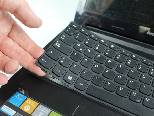 Continue using the plastic opening tool to pry around the edge  until the keyboard is completely freed form the frame.