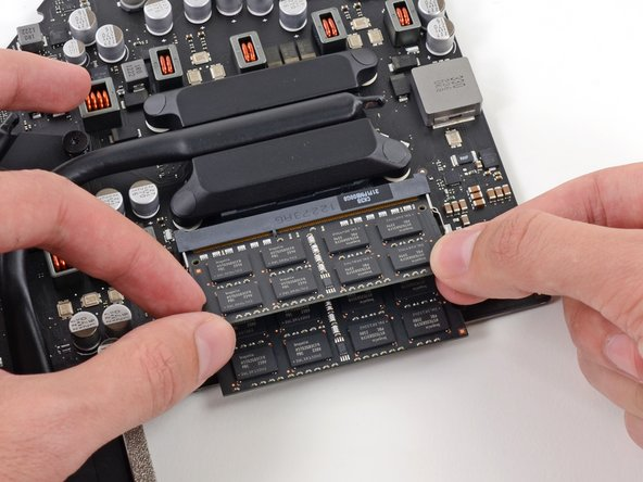 Flip the logic board over and release the tabs from each side of the RAM