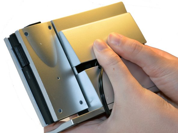 Image 1/3: Using your thumbs, push up on the  battery cover.