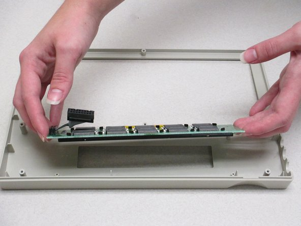 Image 3/3: Lift the display screen and motherboard from the plastic front panel to separate the two pieces.