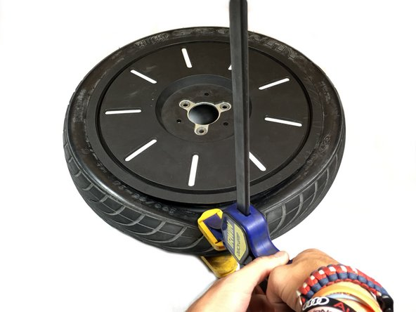 Use the clamp to squeeze the rubber of the tire until the tire pops off of the rim. Repeat this process until the whole tire is popped off of the rim.