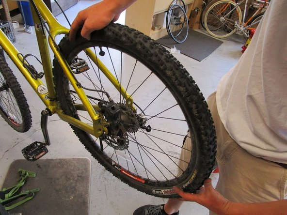 Push down on the the tire with your hands to remove it from the frame of the bike.