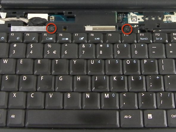 Under the panel, locate and remove the two screws that connect the keyboard to the laptop. One screw is located above the F5 button, and the other one is located above the F10 button.