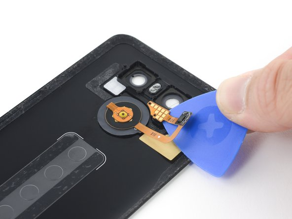 Use an opening pick to pry the contact pad off of the rear case.