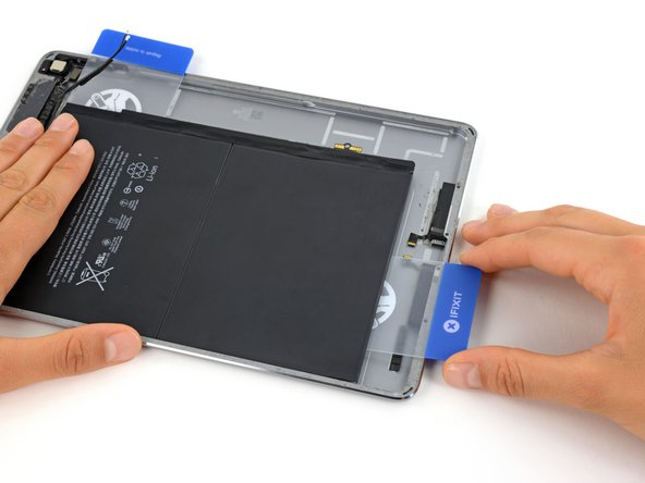 Image 2/2: You may need to reheat the iOpener and lay it across the bottom of the iPad to soften the adhesive securing the bottom edge of the battery.
