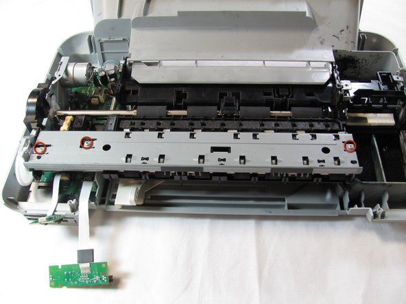Image 1/2: Remove the three T10 12mm Torx screws holding the paper guide to the printer body.