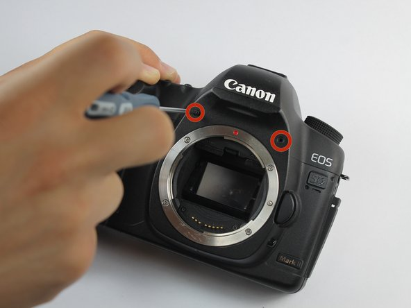 Remove the two 4.8 mm screws above where the lens would be using a Phillips #0.