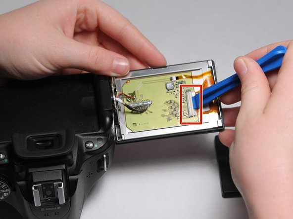 Use the plastic opening tool to pop up the latch holding the ribbon cable on the right side of the circuit board, and remove it.