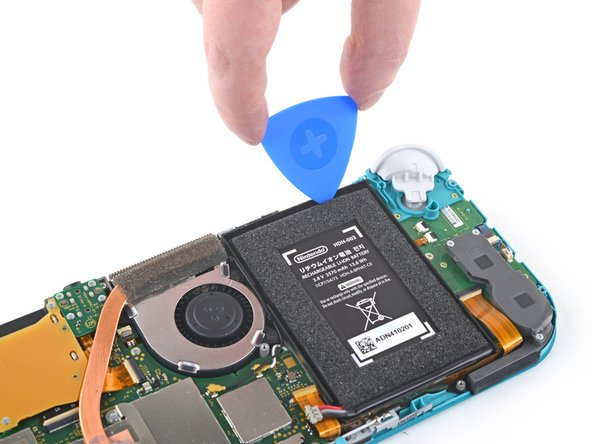 Insert an opening pick into the gap between the battery and the wall of the battery well.