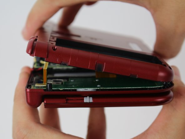 To separate the cover, carefully lift it up and away from the hinges (in order to clear the headphone port), then pivot it towards the hinges to expose the circuit boards.