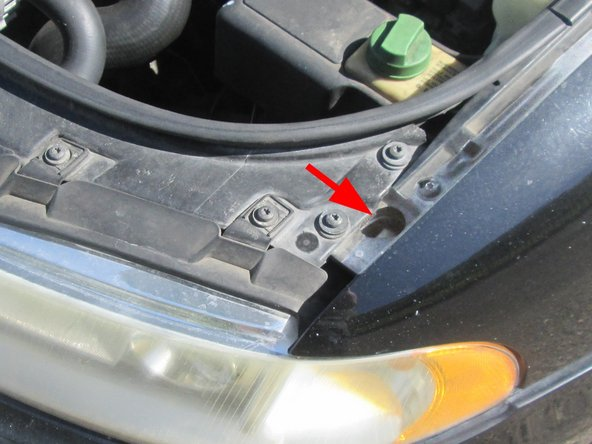 Image 2/3: Unscrew the hidden screw through the hole to the right of the assembly. (Make sure not to lose it in the engine compartment when it comes out.)