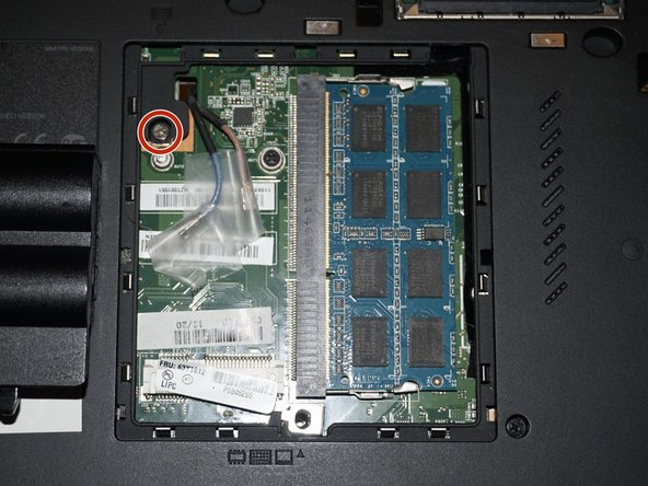 To access the memory module under the keyboard, remove the silver screw securing the keyboard.