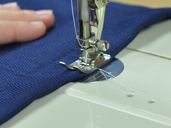 Insert your fabric into the sewing machine and depress the presser foot.