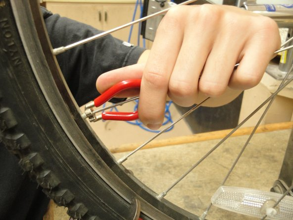 Image 2/2: In the photo, the red marked spokes are being tightened, and the blue marked spokes are being loosened. This will shift the rim closer to the viewer.