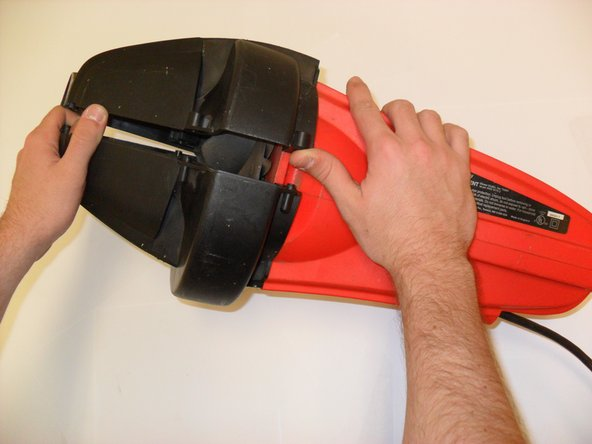 Using your hands, remove the blower tube and clamshell.