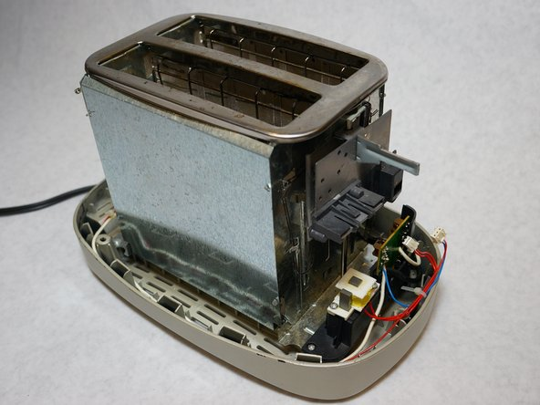 Carefully lift the outer metal shell at an angle so as not to damage the components in the front of the toaster.