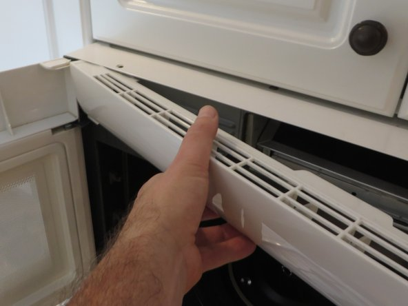 To remove the exhaust fan cover, first pull it from the right side, until it is at the angle shown in the photo.  Then pull it away moving it to the right (to slide out without hitting the microwave door).