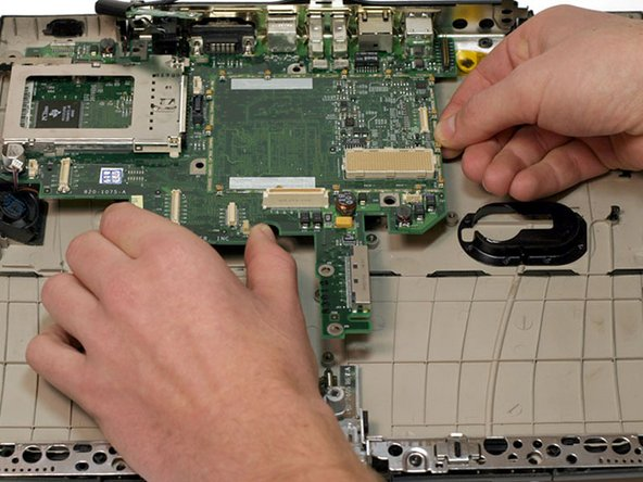 Image 1/1: There are two major obstacles to avoid when removing the logic board: the first is the fan and connector cables, and the second is the bolt in the back left corner.