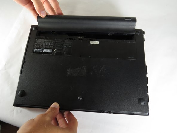 Flip the laptop upside down and remove battery by pressing inward on the two latches holding the battery in.
