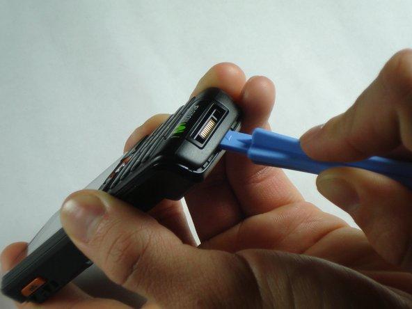 Insérez l'outil d'ouverture en plastique entre le boîtier avant et le boîtier arrière.