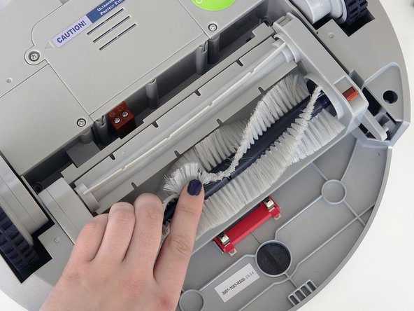 Grip the brush compartment and pull down to reveal two screws on a red fastener. Remove them with the screwdriver.