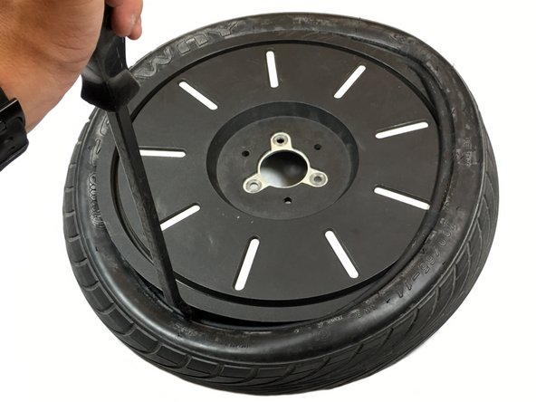 Continue pulling the rubber over the rim until the edge of the rubber is visible all the way around the tire.