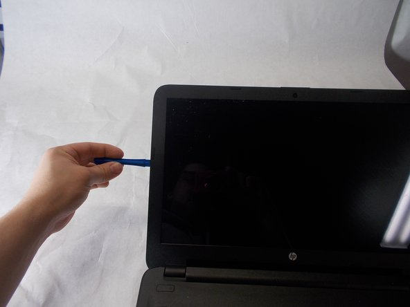 Carefully use the blue plastic opening tool to remove the outer frame of the screen.
