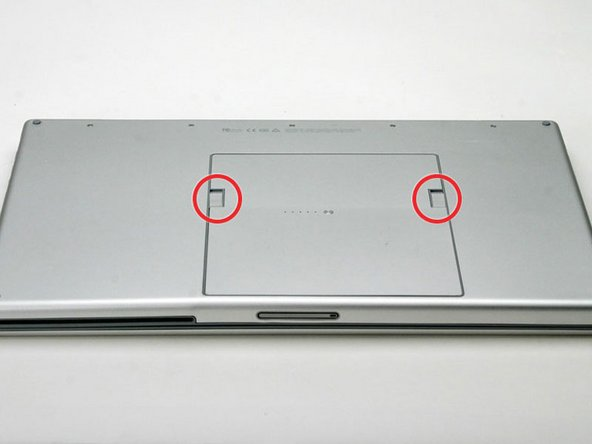 Image 1/1: Use your thumbs to push both battery release tabs away so that the edge of the battery lifts up.