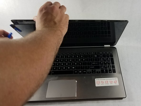 Pry the front panel away from the screen, leaving adjacent edges touching near the hinge of the laptop