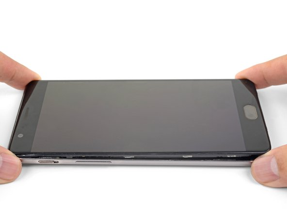With the bottom and left edge of the phone freed, gently wiggle the frame to release the top and right edge clips.