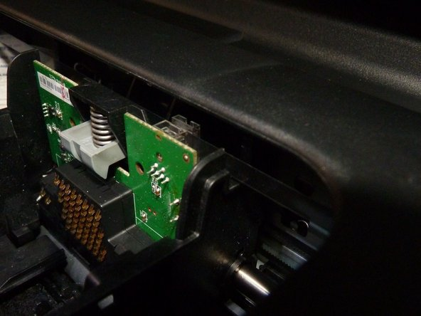 Image 1/3: The circuit board should slide forward and up past the grey sprung catch (Image 1) to reveal the back of the board and the socket without it's ribbon (Image 2 pink arrow)