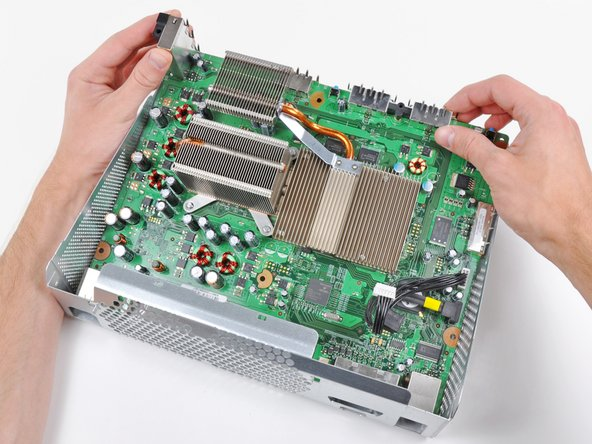Turn the Xbox over, being careful not to let the motherboard fall out of the chassis.
