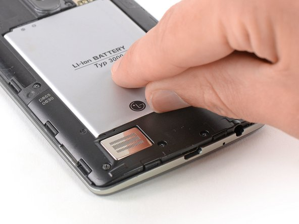 Use a fingernail or a prying tool at the marked notch to lever the battery out of its recess.