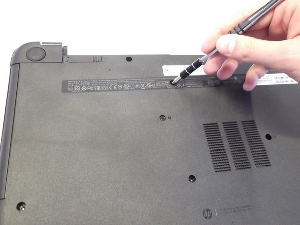 Next locate and unscrew the two 4mm Phllips #1 screws with the keyboard symbol located towards the middle and top of the bottom of the laptop.