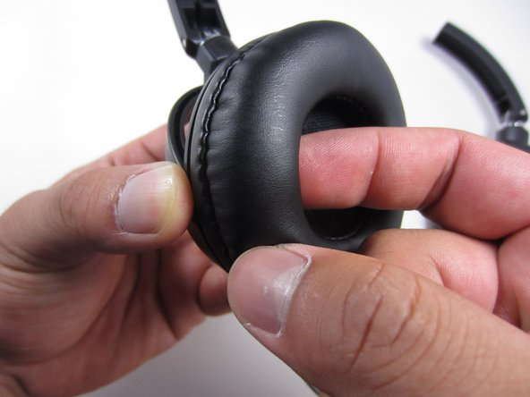 While holding the base of the ear cup with one hand, insert your index finger from your other hand into the inside of the foam ear piece.