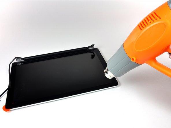 Avec le pistolet à air chaud, ramollissez la colle sous la bordure noire du côté du coin supérieur gauche de la vitre.